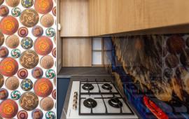 На фото современная кухня с акцентным стеклянным фартуком, фасады МДФ матовая эмаль, фурнитура Blum, дизайнер